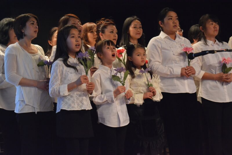 "Members of the Sakura Chorus Mile High , singing ""Hana wa saku"" (""Flowers Will Bloom"")"