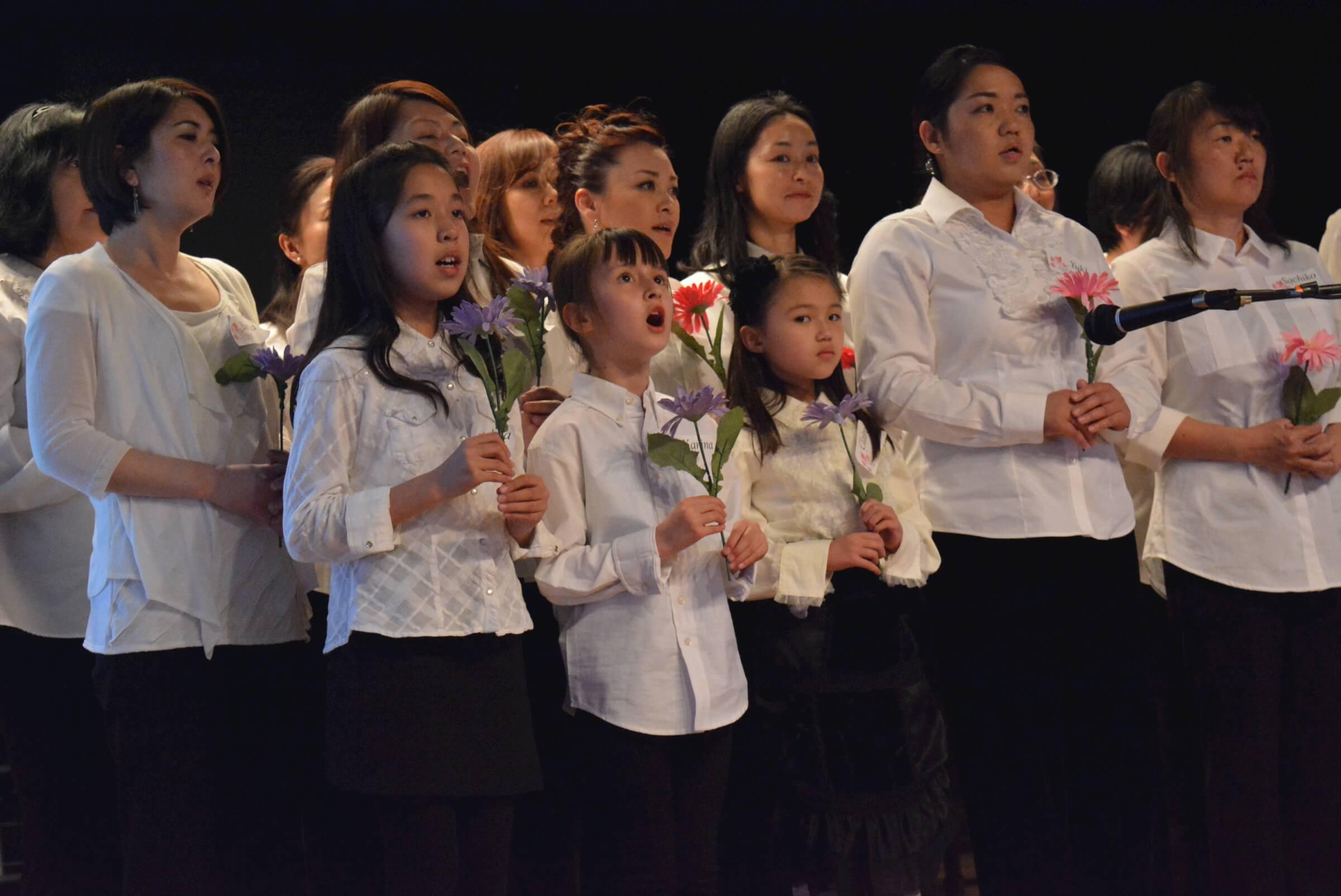 "Members of the Sakura Chorus Mile High , singing ""Hana wa saku"" (""Flowers Will Bloom"")"